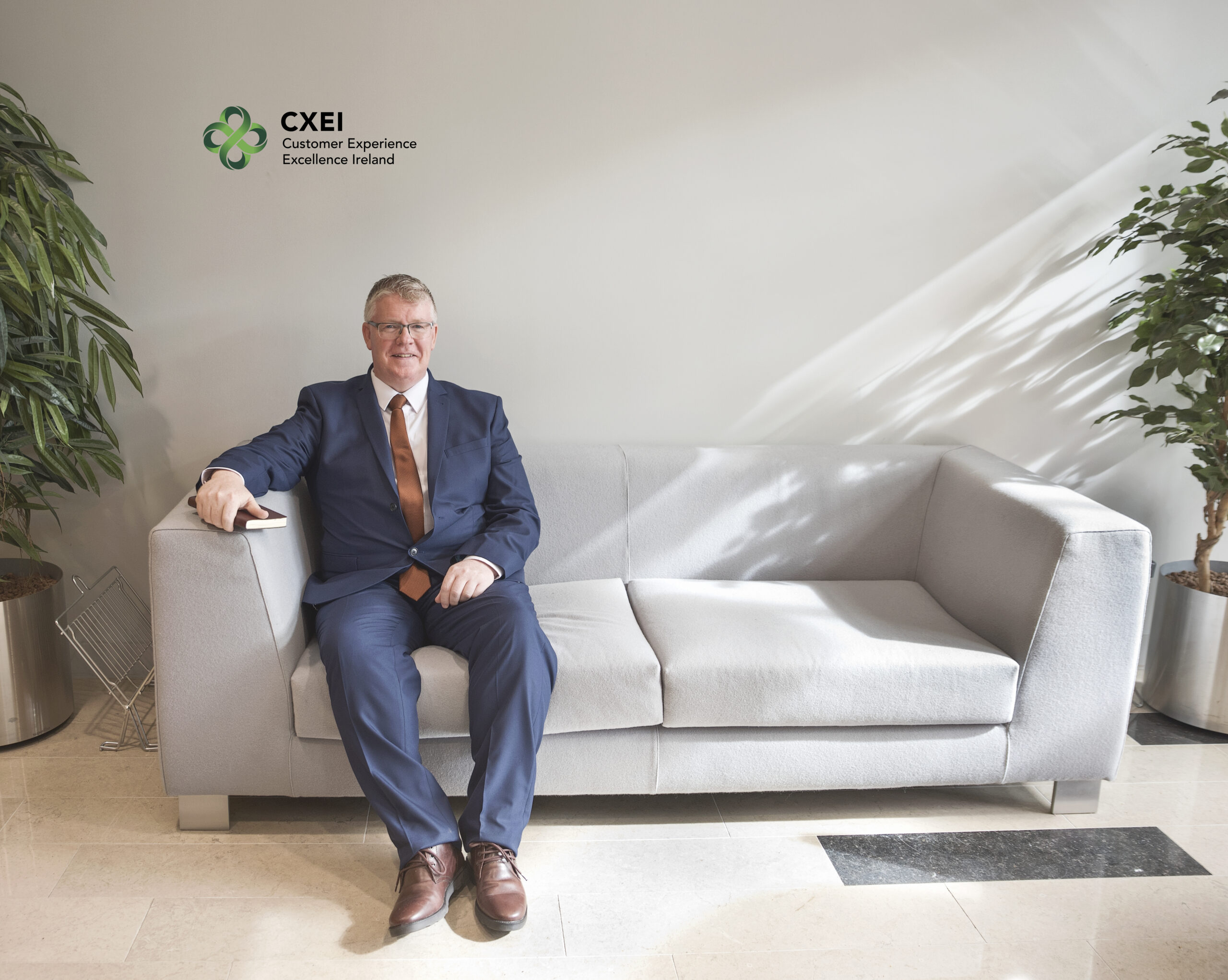 Charlie Boyle, CEO of CXEI, sitting on couch in office, Coloured